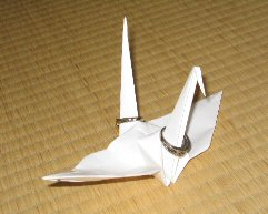 Origami crane, bearing the wedding rings