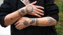 Tattooed arms of a Catholic lady in Bosnia and Herzegovina